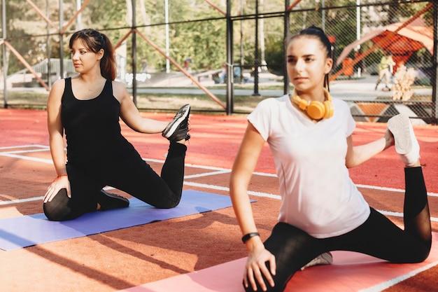 Bella donna plus size che fa stretching con la sua ragazza al mattino in un parco sportivo prima del cardio.