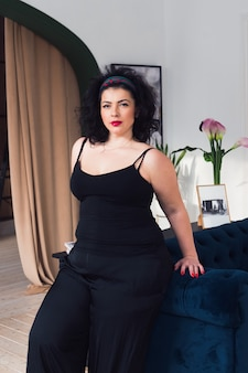 Bella plus size donna in posa alla fotocamera donna sicura di sé che indossa un abito nero