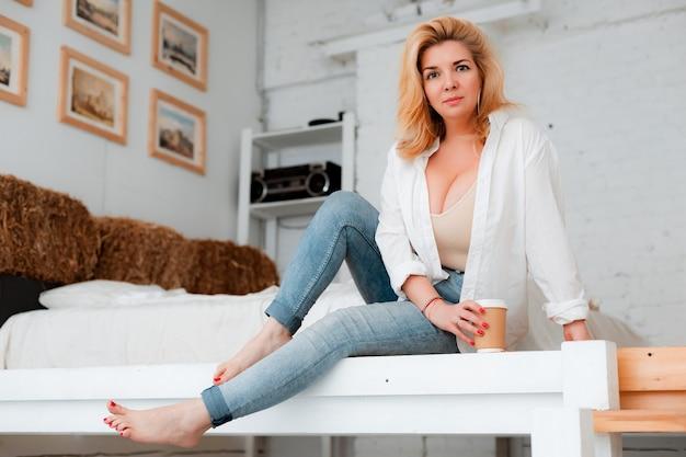 Bella donna plus size si siede su un pavimento bianco con caffè. corpo positivo