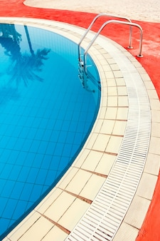 Bella piscina con gradini vicino al mare sullo sfondo della natura