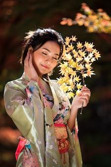 Bello ritratto della donna asiatica che indossa il kimono del giappone nel parco