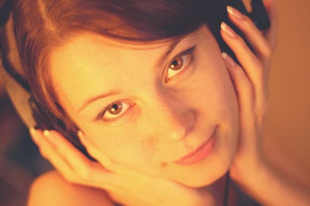 Bello ritratto di una ragazza in primo piano delle cuffie