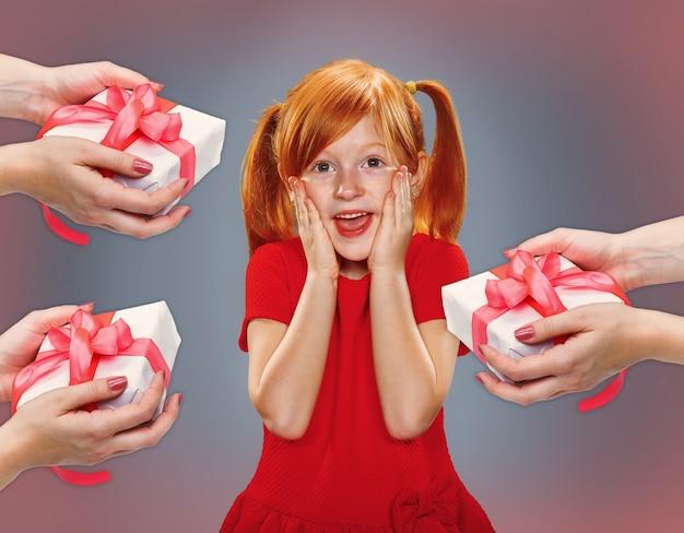 Il bellissimo ritratto di una bambina sorpresa con i capelli rossi in abito rosso su blu con regali