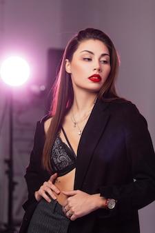 Bello ritratto modello di moda giovane donna con labbra rosse con capelli lunghi in cappotto nero alla moda in reggiseno di pizzo sexy in posa vicino al muro in studio con lampada luminosa. ragazza bruna europea al chiuso.