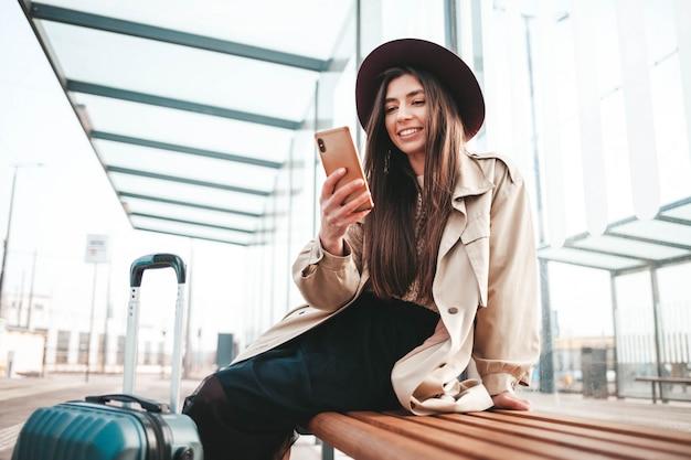 Viaggiatore bella ragazza positiva in cappotto e cappello in testa, seduto a una fermata dell'autobus in attesa di un autobus e utilizza uno smartphone. concetto di tecnologia mobile
