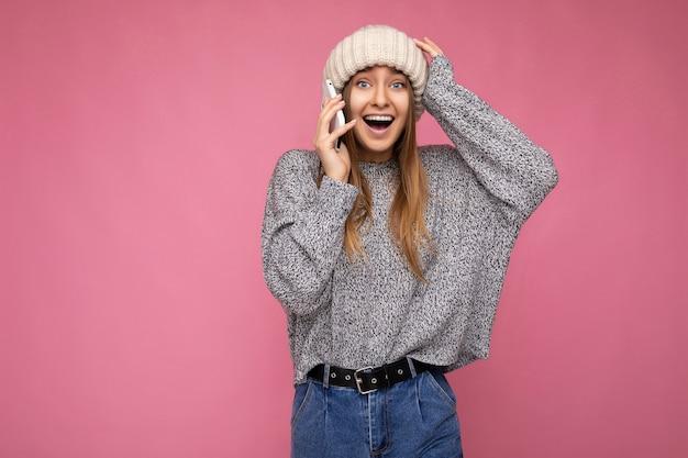 Bella positiva felice stupita giovane donna bionda che indossa un maglione grigio casual e un cappello beige