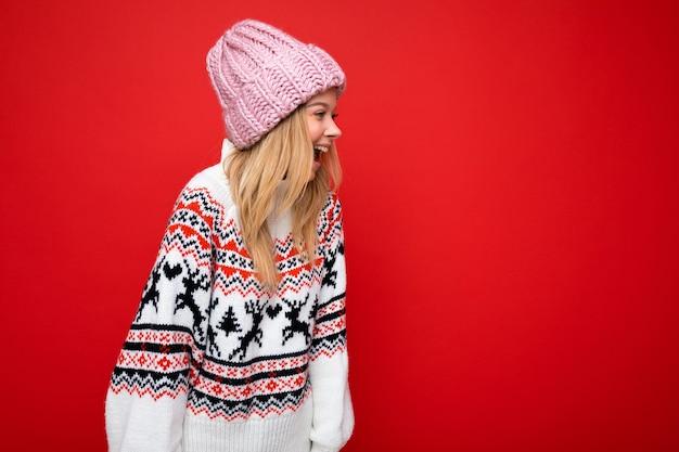 Bella giovane donna bionda felice positiva isolata sopra la parete variopinta del fondo che porta i vestiti alla moda casuali che provano le emozioni sincere che guardano al lato. spazio vuoto, copia spazio