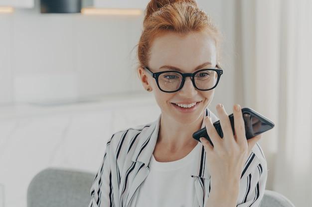 Bella donna dai capelli rossi positiva con gli occhiali che tiene il telefono cellulare e invia un messaggio audio