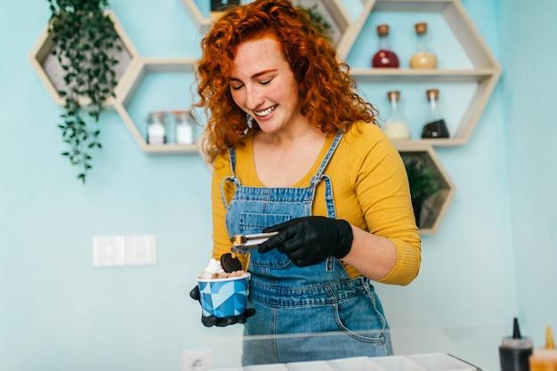 Bella e positiva donna rossa allo zenzero che sorride e lavora in una gelateria artigianale. lei prepara e serve deliziosi dolci.