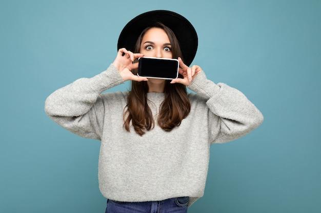 Bella donna positiva che indossa un cappello nero e un maglione grigio gray