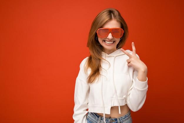 Bella giovane donna bionda positiva che indossa abiti casual e occhiali ottici alla moda isolati