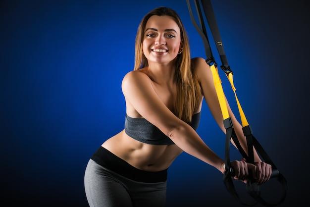 Modello di fitness bella ragazza giovane positivo in posa in studio aggrappato a cinghie appese
