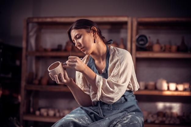 Bellissimo maestro ceramista che fa ceramica, scultore di argilla bagnata su ruota