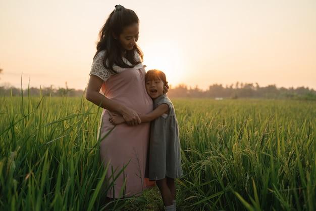 Bella donna asiatica incinta con la figlia che gioca sulla sua pancia