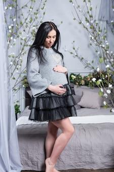 Bella donna incinta del brunette in un vestito che tiene le mani sulla pancia che sta vicino al letto con i fiori sul letto in camera da letto. ultimi mesi di gravidanza.