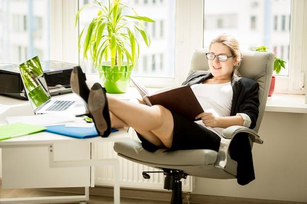 Bella donna di affari incinta che posa sulla sedia alla finestra