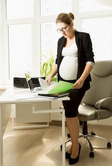 Bella donna d'affari incinta in piedi alla scrivania dell'ufficio