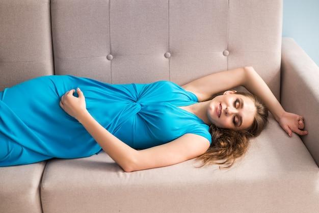 Bella donna incinta in un vestito blu è sdraiata sul divano