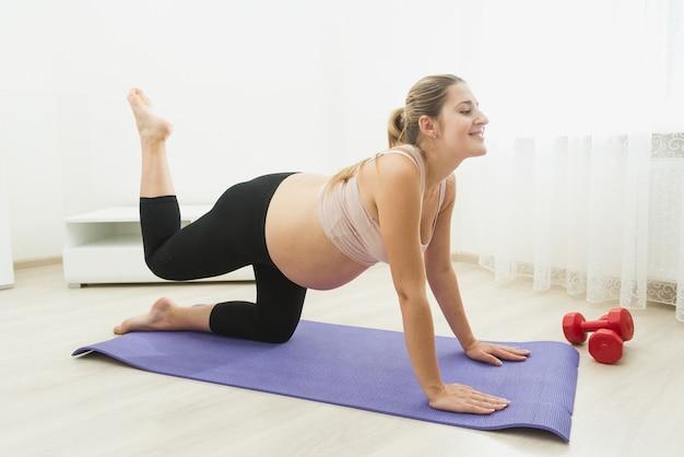 Bella donna incinta che fa esercizi di yoga sul tappetino fitness