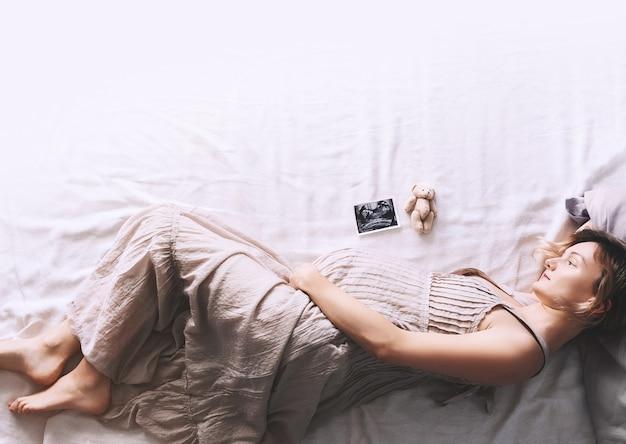 Bella donna incinta in abito che si tiene per mano sulla pancia sdraiata su un lato di profilo a letto