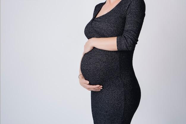 Bella donna incinta in un abito in piedi toccando la sua pancia