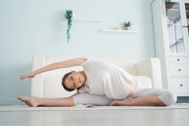 Bella donna incinta che si esercita mentre si siede nella posizione del loto. esercizi prenatali.