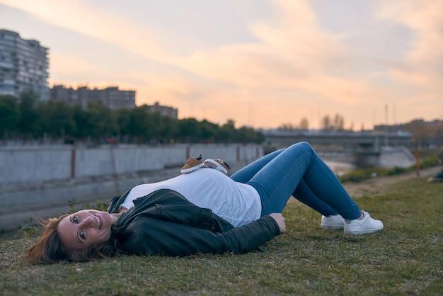 Bella donna incinta sdraiata sull'erba durante il tramonto in città. giovane adulto.
