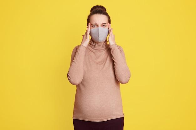 Bella donna incinta in mascherina medica tenendo le dita sulle tempie, soffre di mal di testa, avendo paura di essere infettato dal virus corona, indossa casualmente, posa contro il muro giallo.
