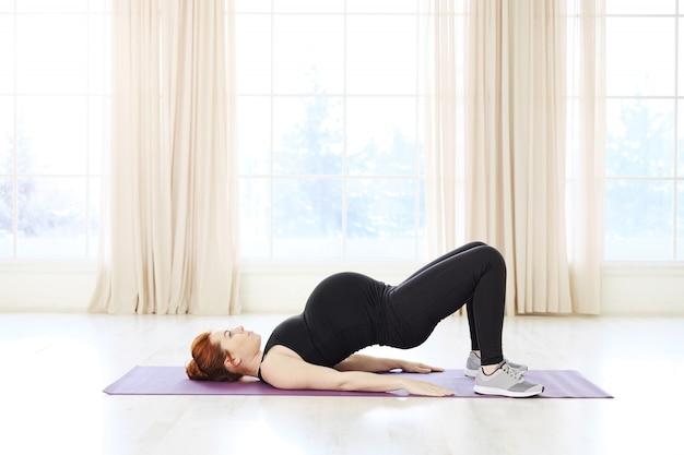 Bella donna incinta che pratica yoga o pilates prenatale