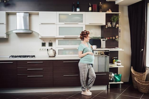 Bella donna incinta che si rilassa a casa con una tazza di tè