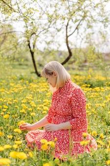 Bella donna incinta rilassante nel parco che indossa un abito rosso