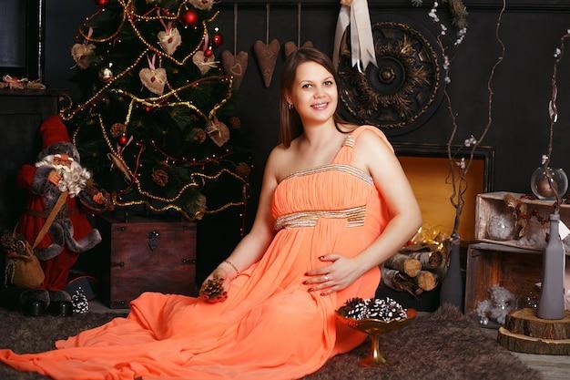 Bella donna incinta in abito da sera intelligente vicino all'albero di natale