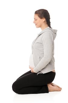 Bella donna incinta che sorride e che fa esercizi isolati