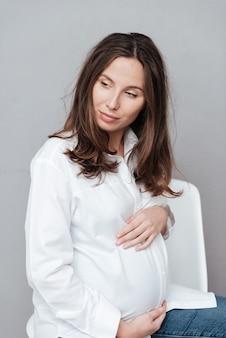 Bella donna incinta in studio che distoglie lo sguardo sfondo grigio