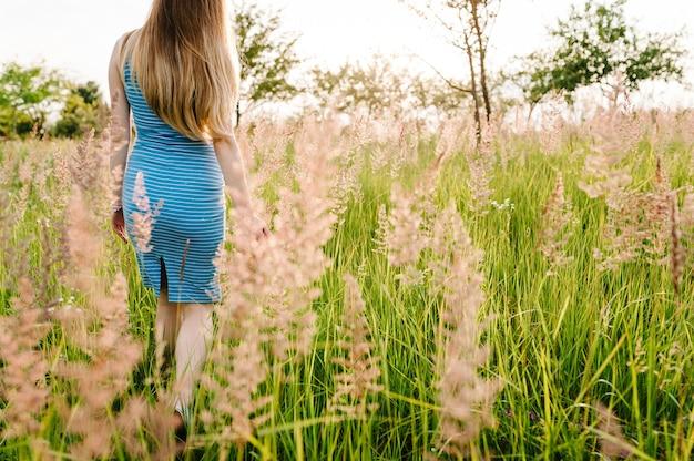 Bella donna incinta in abito estivo alla moda andare a piedi in campo con i fiori alla luce del sole, godendo la sensazione.
