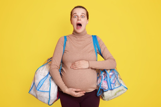 Bella donna incinta che tocca la sua pancia in piedi isolata sopra il muro giallo, tiene la bocca ampiamente aperta, sente le contrazioni. deve andare all'ospedale di maternità, tiene le borse con le cose.