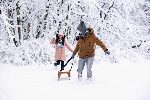 Una bella donna incinta in abiti pesanti lancia palle di neve al marito