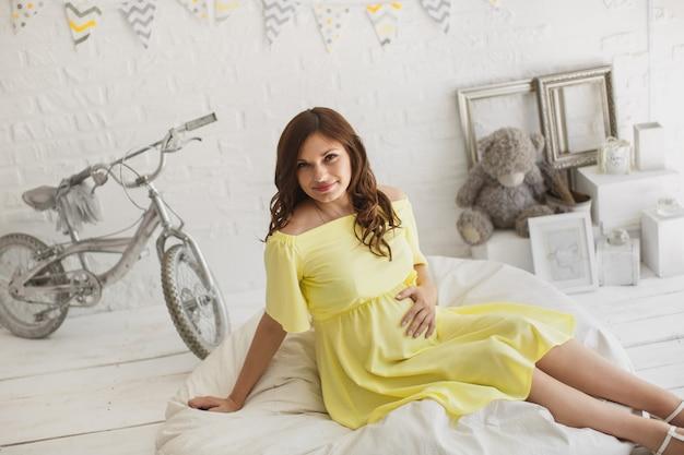 Bella donna incinta in un vestito giallo in studio.