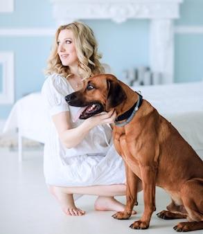 Bella giovane donna incinta con il suo animale domestico seduto sul letto in camera da letto