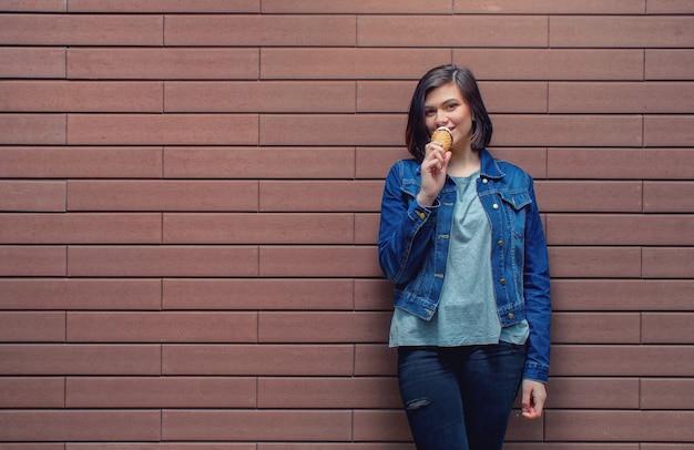 Bella bella ragazza caucasica in una giacca di jeans blu assaggia il delizioso gelato gustoso vicino a un muro di mattoni strutturato.