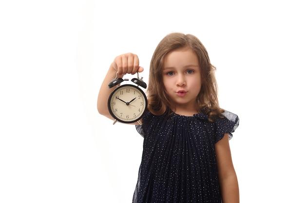 Bella bella bambina europea di 4 anni con una sveglia in mano e guarda la telecamera, isolata su sfondo bianco con spazio per le copie