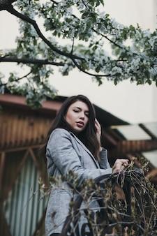 Bella bella ragazza con lunghi capelli ricci in piedi all'aperto, sullo sfondo della città