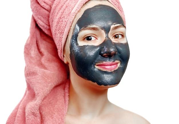 Bella ragazza abbastanza sexy con maschera facciale nera su sfondo bianco, ritratto del primo piano, isolato, ragazza con un asciugamano rosa in testa, ragazza sorride, maschera nera sul viso della ragazza, gode