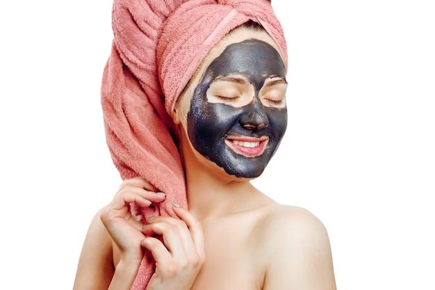 Bella ragazza abbastanza sexy con maschera facciale nera su sfondo bianco, ritratto di close-up, isolato, ragazza con un asciugamano rosa in testa, ragazza sorride, maschera nera sul viso della ragazza, gode