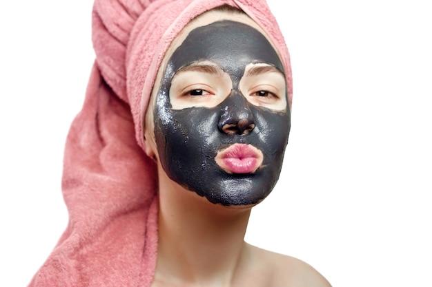 Bella ragazza abbastanza sexy con maschera facciale nera su sfondo bianco, ritratto di close-up, isolato, ragazza con un asciugamano rosa in testa, ragazza manda un bacio d'aria, maschera nera sul viso della ragazza
