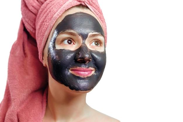 Bella ragazza abbastanza sexy con maschera facciale nera su sfondo bianco