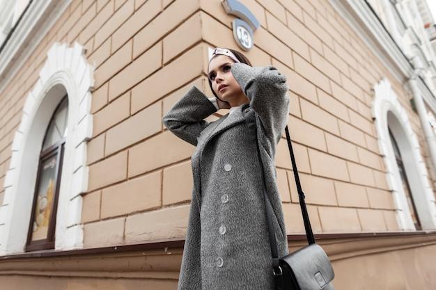 Bellissima modella di moda giovane donna in capispalla casual primaverile alla moda in elegante bandana si trova vicino a un edificio d'epoca sulla strada della città. attraente ragazza alla moda in voga indossare in posa all'aperto.