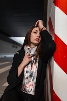 Bella bella giovane donna con capelli castani in elegante cappotto nero in elegante scialle di seta vintage sta riposando vicino a un pilastro rosso-bianco in un parcheggio cittadino. modello di moda attraente ragazza europea.