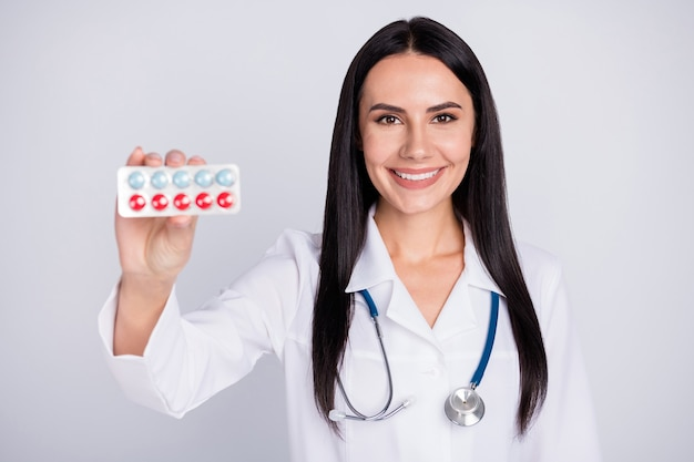 Bella signora professionale doc proponendo pillole su sfondo grigio