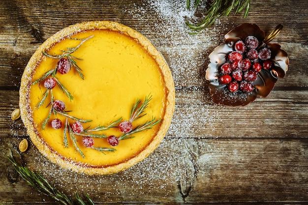 Bella torta di zucca con mirtilli rossi su sfondo di legno. copia spazio.